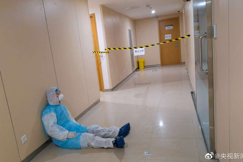 中國武漢肺炎抗疫第一線,成都市溫江區人民醫院的放射科醫師張銳,連續工作20小時後,坐在地上睡著了(微博)