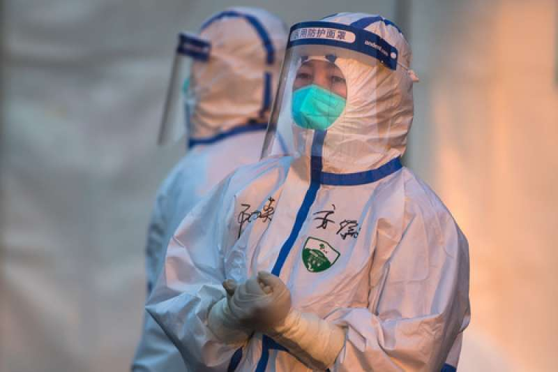 中國武漢肺炎疫情,2月12日,來自安徽醫療隊的陳荔英(右)在武漢體育中心方艙醫院門口等待轉運來的患者。(新華社)