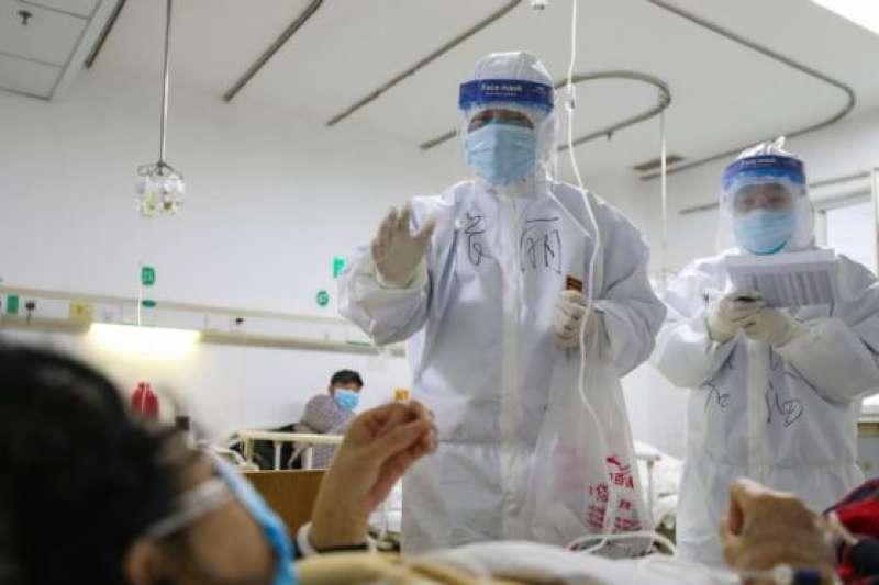 武漢金銀潭醫院的醫護人員正在檢查一名新冠肺炎患者的身體狀況。(BBC中文網/GETTY IMAGES)