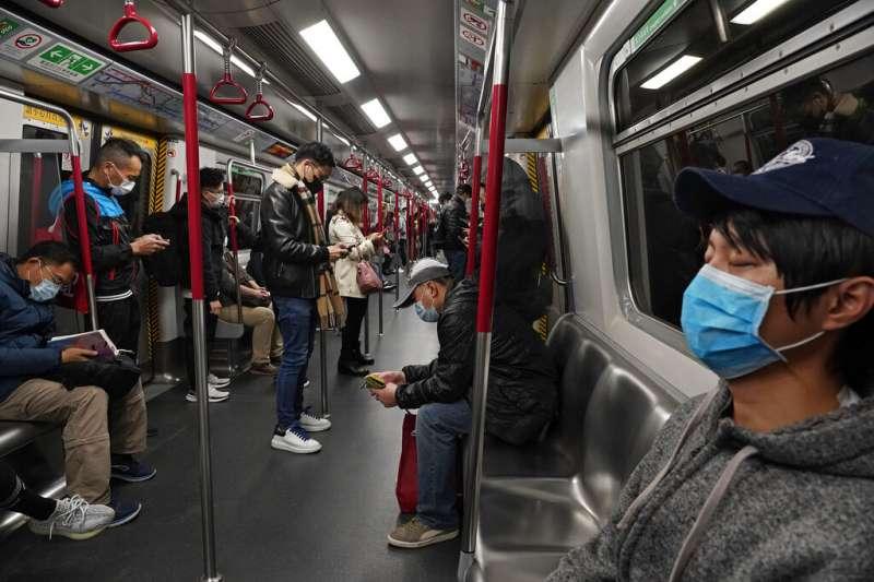 香港大學醫學院院長梁卓偉推算,若出現1宗死亡個案,可能就代表當地已經有100宗確診病例。圖為香港地鐵裡戴著口罩的乘客。(資料照,美聯社)