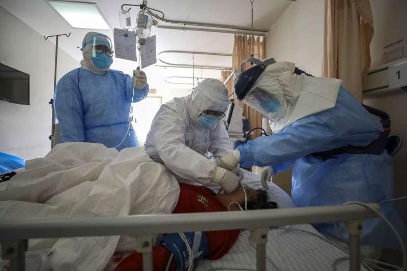 中國湖北省武漢市,醫護人員正在檢查一位感染新冠病毒肺炎的患者。新冠肺炎、武漢肺炎。(AP)
