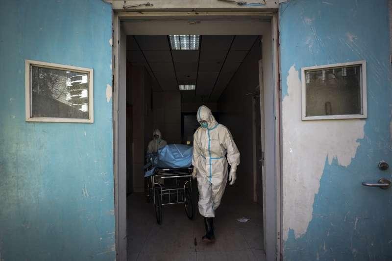 中國湖北省武漢市,醫護人員挪送一位因新冠肺炎而死的病患。(AP)