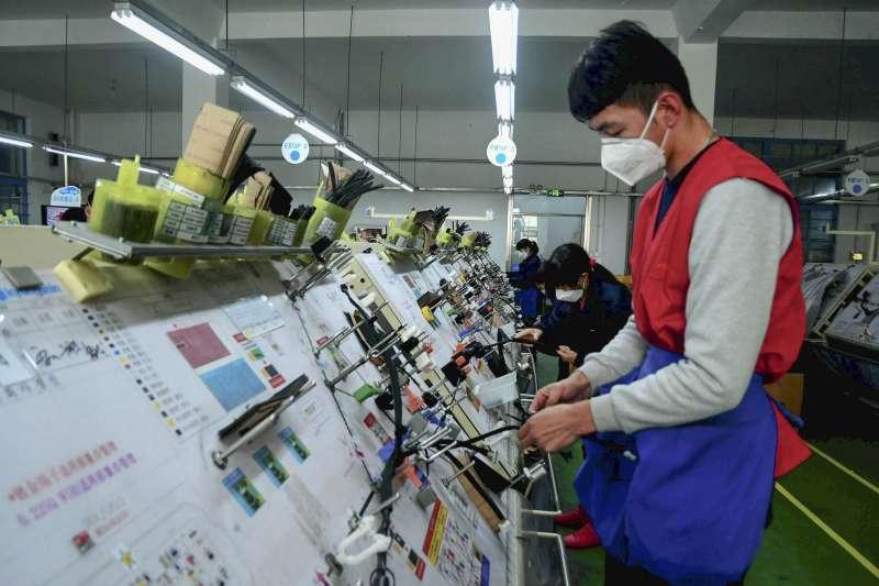 中國經濟受到新冠肺炎疫情影響而重挫,圖為山東省部分工廠戴著口罩復工。武漢肺炎。(AP)