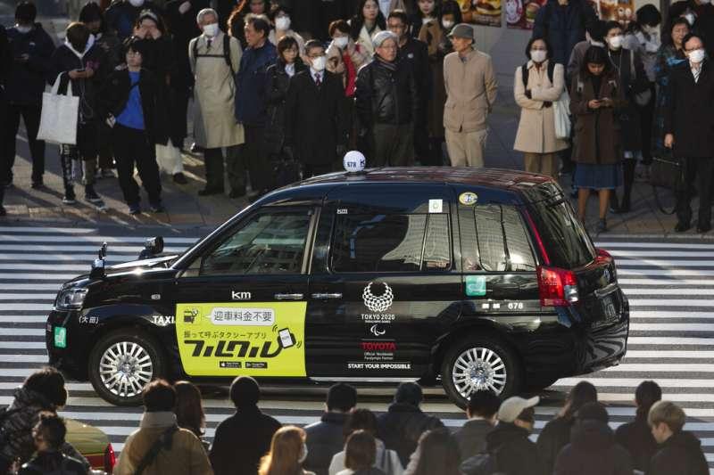 一輛東京街頭的計程車已經畫上了2020東京奧運標誌,但「東奧還會不會辦」如今卻陷入巨大的不確定之中。(美聯社)