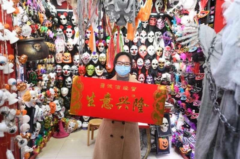 義烏國際商貿城的商戶吳紅英在店鋪內展示領取的「生意興隆」橫幅。(新華社)