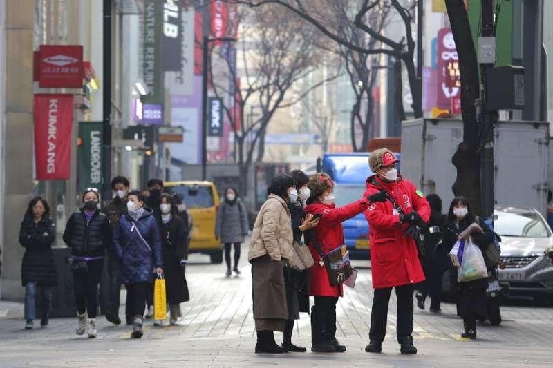 南韓21日宣布新增52例武漢肺炎確診病例,全國共計感染人數來到156例。圖為帶著口罩在首爾遊玩的旅客。(美聯社)