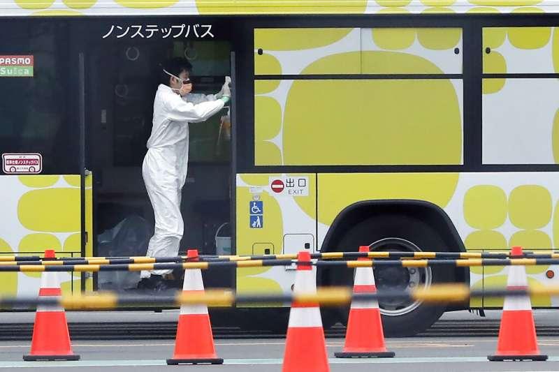 鑽石公主號陸續上檢查結果陰性的旅客下船,工作人員正在對載運過旅客的巴士進行消毒。(美聯社)