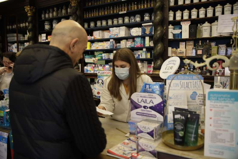 義大利北部倫巴底大區科多諾傳出武漢肺炎疫情,當地藥局人員戴著口罩(美聯社)