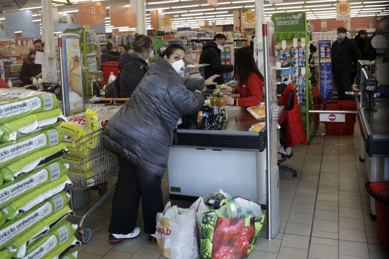 義大利新冠肺炎疫情延燒,北部倫巴底大區成為重災區,該區卡薩爾普斯泰爾倫戈鎮居民戴著口罩到超市採買(美聯社)