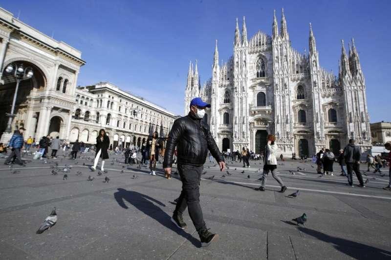 義大利疫情迅速攀升,米蘭鬧區的旅客也紛紛戴起口罩。(美聯社)