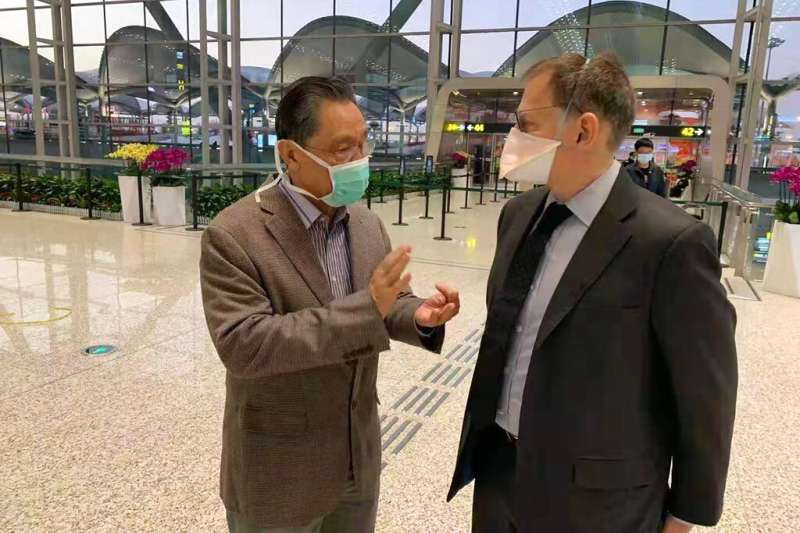 中國國家衛健委高級別專家組組長、中國工程院院士鍾南山(左)與美國專家在廣州機場討論疫情。(美聯社)