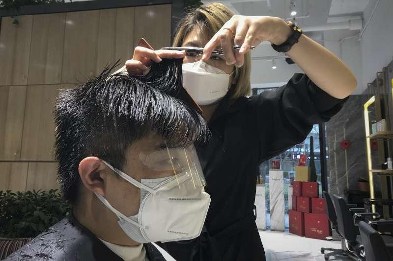 中國武漢肺炎(新冠肺炎)疫情持續延燒,北京一間髮廊的設計師與顧客剪髮時皆戴上口罩(AP)