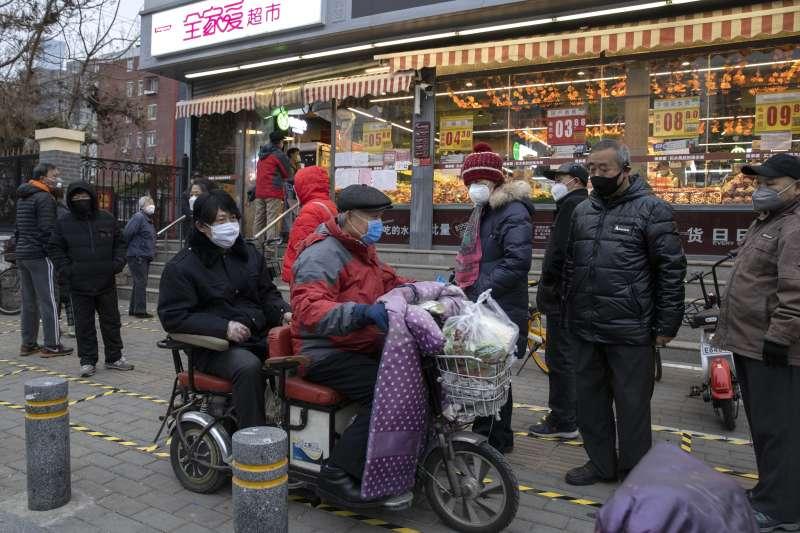 中國武漢肺炎(新冠肺炎)疫情持續延燒,北京市民上街採買時皆戴上口罩(AP)