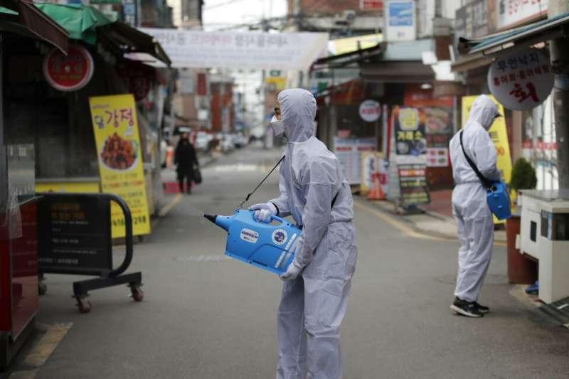 南韓武漢肺炎確診人數已衝破千人大關,圖為穿著防護服的工作人員在首爾街頭進行消毒。(美聯社)