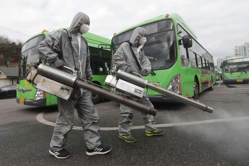 南韓武漢肺炎確診人數已衝破千人大關,圖為穿著防護服的工作人員在首爾巴士總站進行消毒。(美聯社)