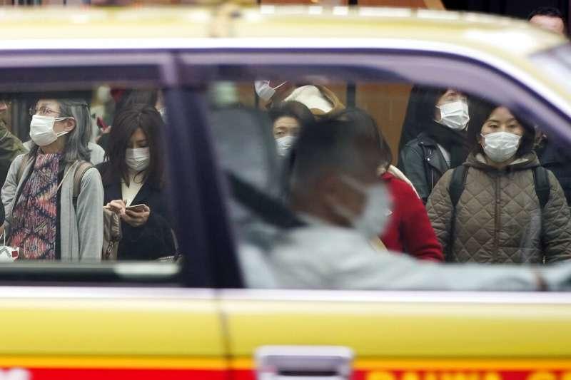 日本武漢肺炎疫情嚴重,銀座的計程車司機與往來行人都戴上口罩。(美聯社)