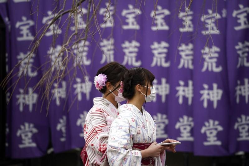 日本疫情嚴重,東京兩名女性遊客也戴著口罩。(美聯社)