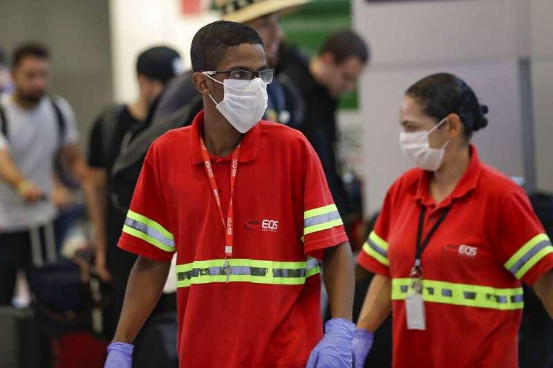 全球新型冠狀病毒疾病(COVID-19,武漢肺炎)病例大爆發,位於南美洲的巴西也淪陷,機場人員戴起口罩。(AP)
