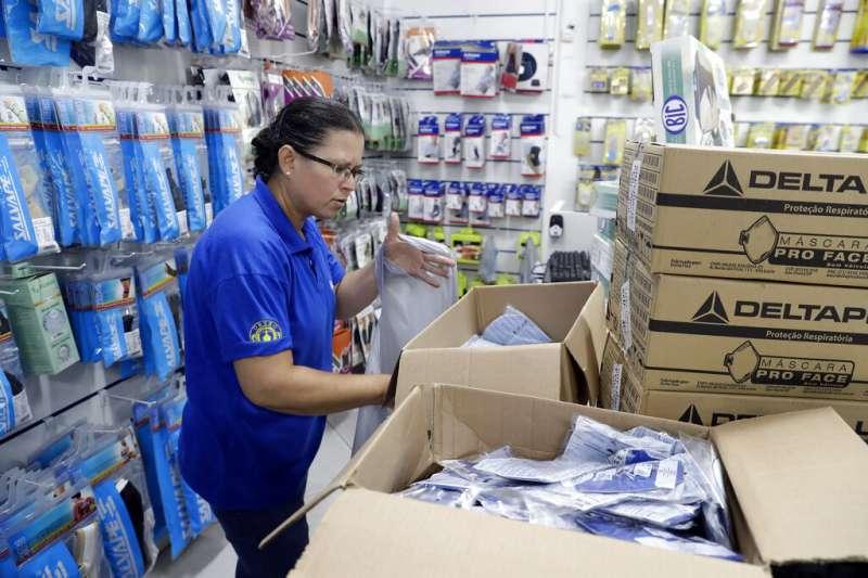 全球新型冠狀病毒疾病(COVID-19,武漢肺炎)病例大爆發,位於南美洲的巴西也淪陷,藥局職員整理口罩庫存。(AP)