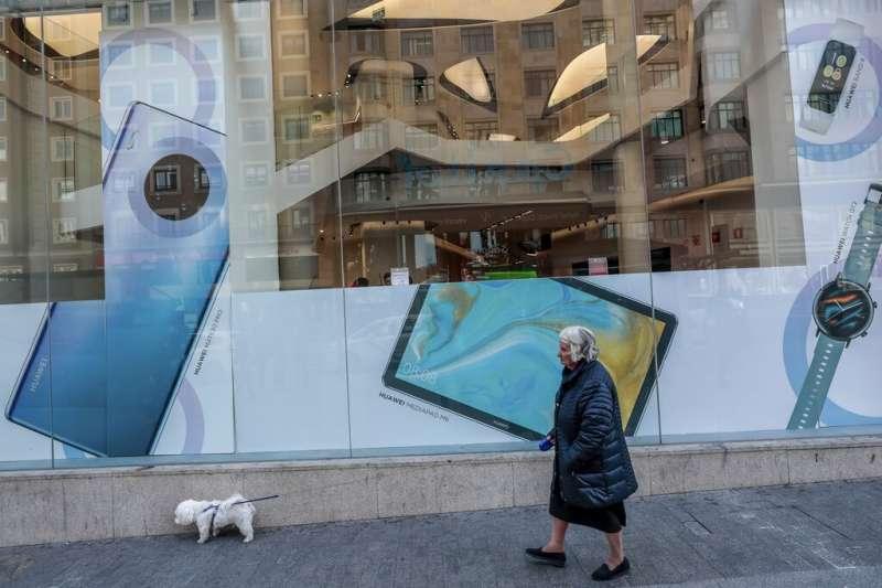 西班牙馬德里一名婦人正在遛狗,牆上貼的是華為的廣告彩繪。(美聯社)