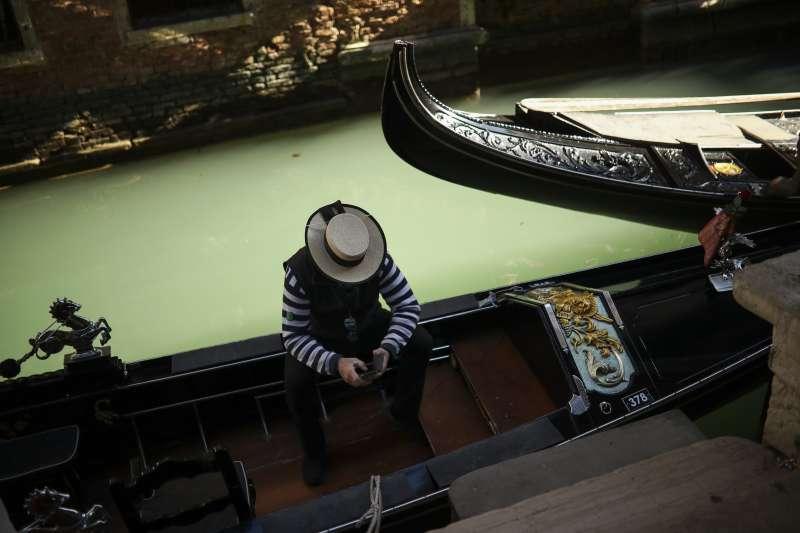 新冠肺炎疫情重創全球經濟。圖為義大利確診病例破千,威尼斯的貢多拉船夫苦無顧客上門。(AP)