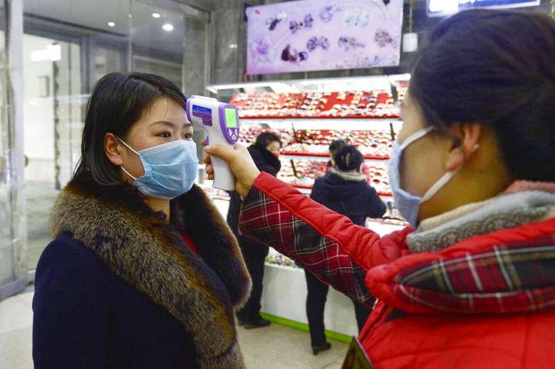 武漢肺炎疫情肆虐,北韓平壤的賣場正在為顧客測量體溫。(美聯社)