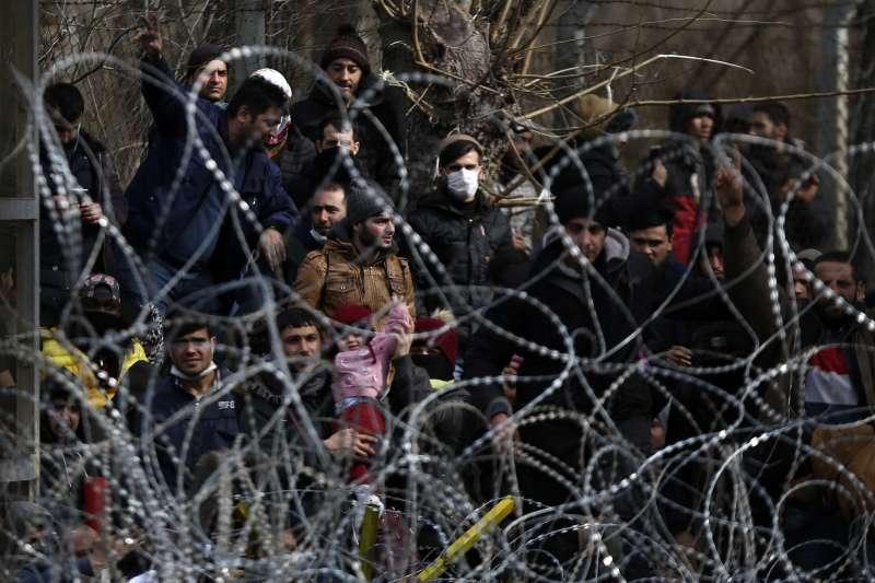 難民企圖通過鐵絲網進入希臘國境。(美聯社)