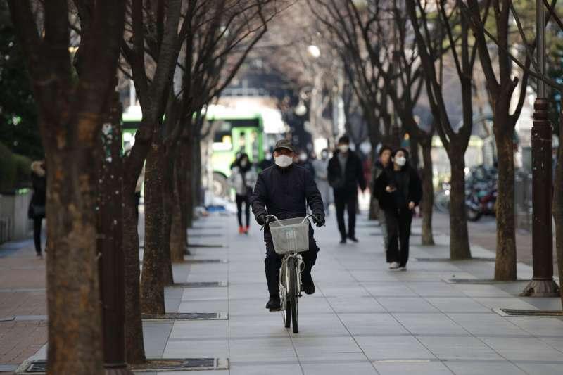 武漢肺炎疫情肆虐,南韓首爾民眾外出仍戴著口罩。(美聯社)