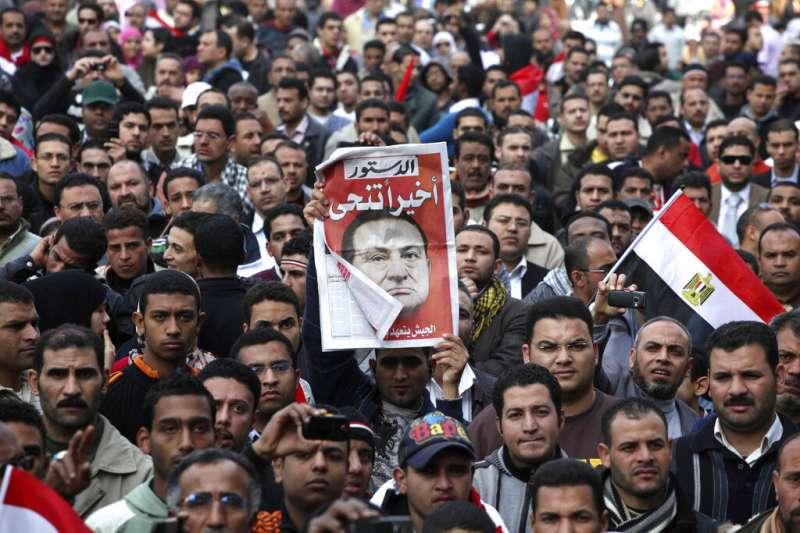 2011年2月12日,開羅的解放廣場上滿是籲求民主人權的年輕人,一位民眾手上拿的報紙頭版用阿拉伯文寫著:他(穆巴拉克)終於下台了。(美聯社)