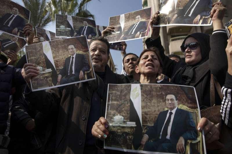 埃及前總統穆巴拉克2月26日下葬,他的支持者在送葬隊伍旁高舉他的肖像。(美聯社)