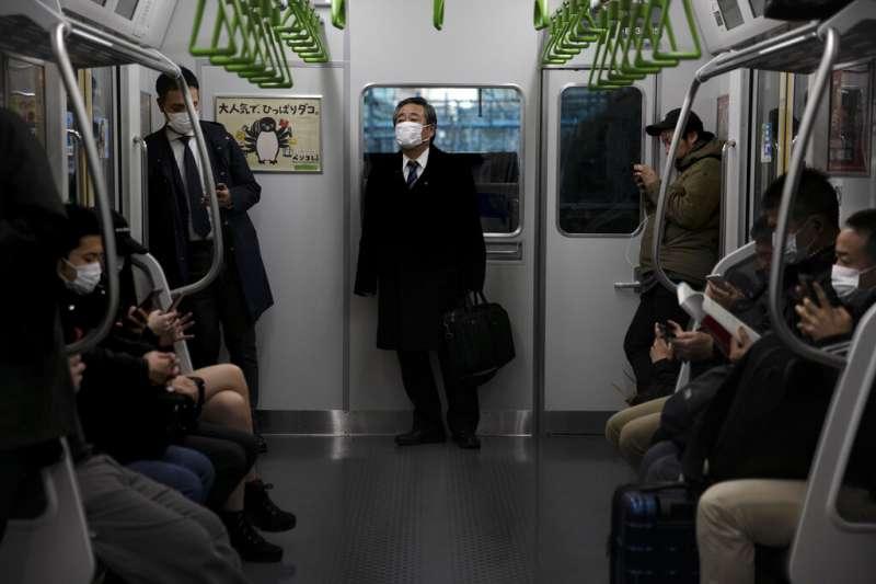 戴著口罩的日本東京地鐵乘客。(美聯社)