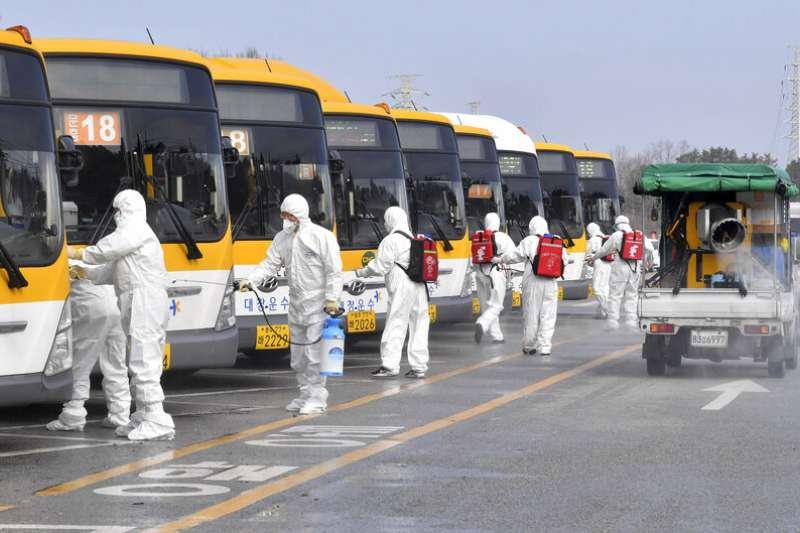 南韓疫情肆虐,工作人員正在光州公車站加強消毒。(美聯社)