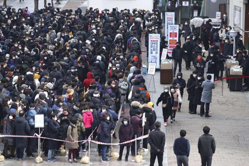 南韓疫情肆虐,首爾購買口罩的人潮大排長龍。(美聯社)