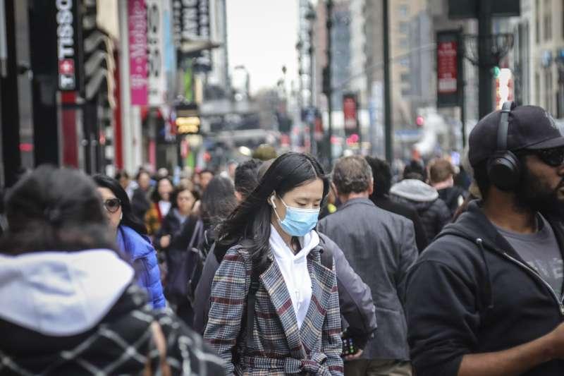 武漢肺炎:美國紐約曼哈頓的繁忙街頭,有行人戴上口罩(AP)