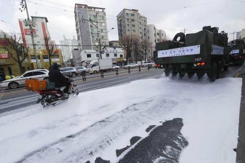 武漢肺炎疫情肆虐,南韓首爾街頭正在加強消毒工作。(美聯社)