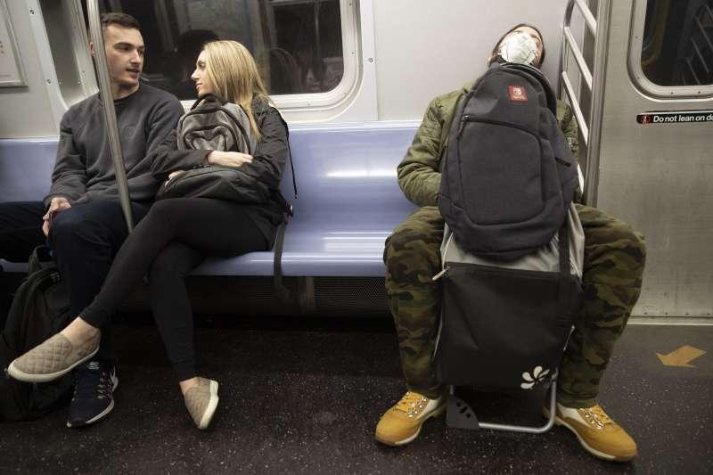 美國新冠肺炎(武漢肺炎)疫情持續升溫,紐約地鐵上的乘客開始戴起口罩(AP)