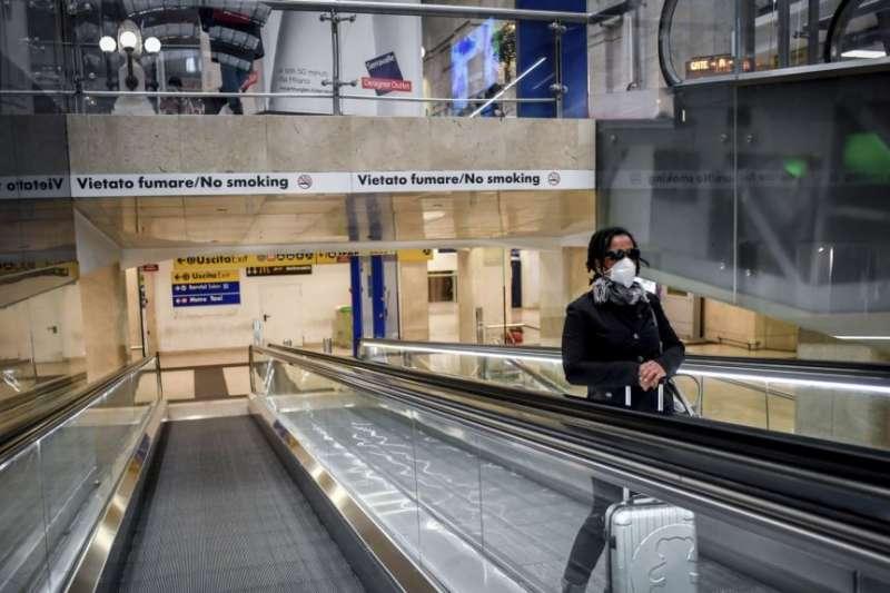 2020年3月8日,一名戴口罩的婦女在米蘭中央火車站的電梯上。(美國之音/AP)