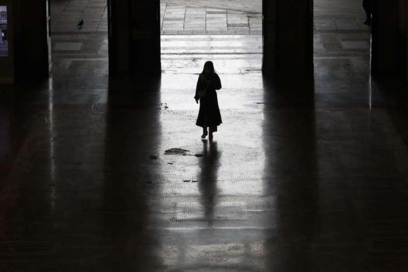 一位孤獨的旅客離開米蘭火車站。(美國之音/AP)