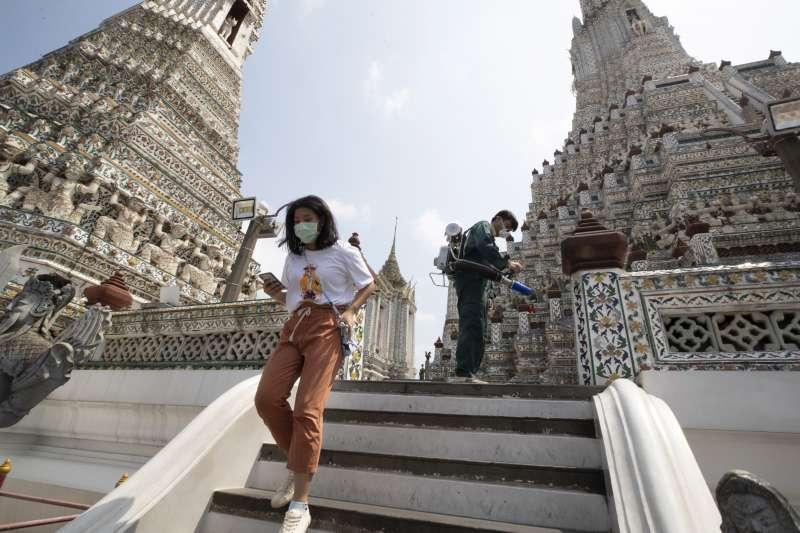 東南亞經濟高度依賴中國,如今受到武漢肺炎疫情衝擊,觀光零售業尤其慘淡,圖為遊客戴著口罩參觀泰國景點。(AP)