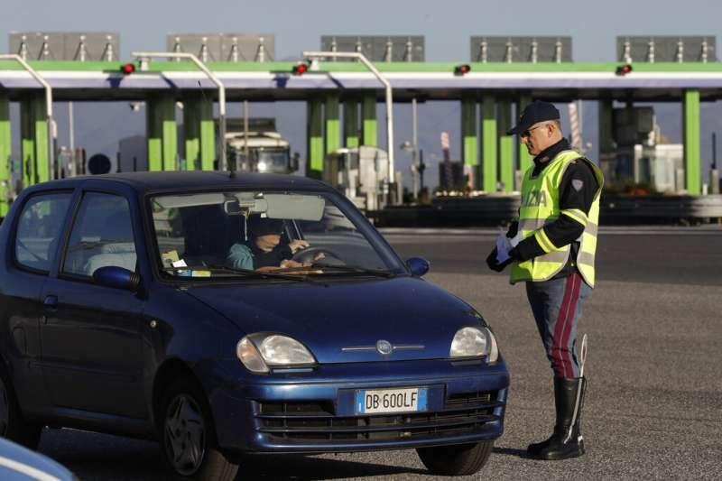 義大利人民被政府要求「留在家中、哪也別去」,一位警察正在羅馬的高速公路收費站查驗往來車輛的相關證明。(美聯社)