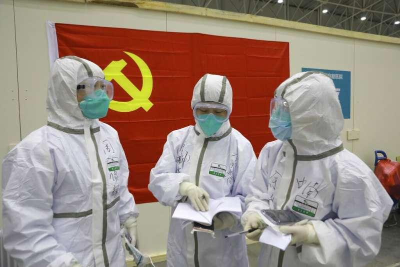 在這張由新華社發布的新聞照片中,醫療人員在中國共產黨黨旗前討論病例。(美聯社)