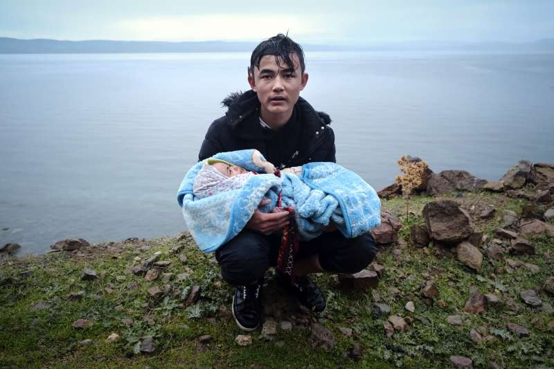 2020年3月,抵達希臘萊斯沃斯島(Lesbos)的敘利亞難民,一名男子抱著嬰兒登陸(AP)