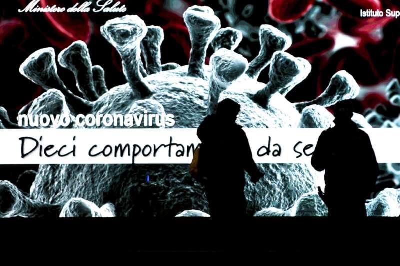 義大利疫情肆虐,圖為米蘭街頭的新冠病毒宣傳海報。(美聯社)