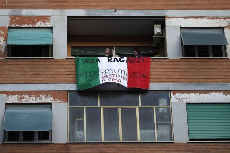 義大利疫情肆虐,但民眾仍在陽台相互加油打氣、掛出「一切都會好轉」的標語。(美聯社)
