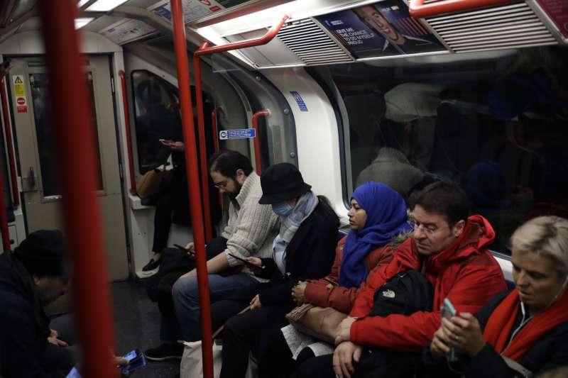 英國的武漢肺炎疫情延燒,一名搭地鐵的婦女戴著口罩(美聯社)