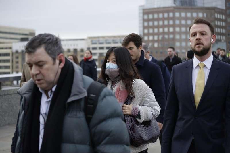 英國的武漢肺炎疫情延燒,路上一名女性行人戴著口罩(美聯社)