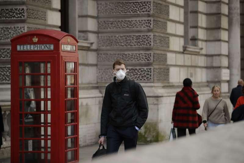 英國的武漢肺炎疫情延燒,倫敦市中心一名男性行人戴著口罩(美聯社)