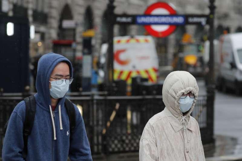 英國的武漢肺炎疫情持續延燒,倫敦地鐵站附近的行人戴著口罩(美聯社)
