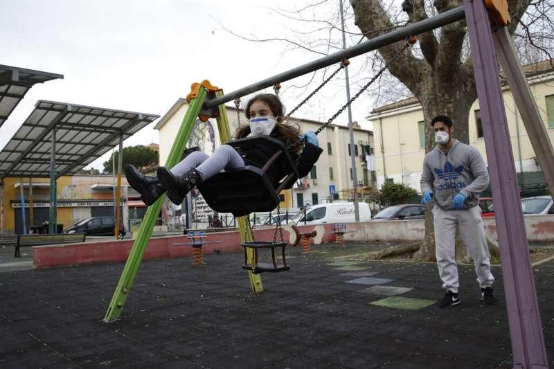 義大利一位爸爸帶著女兒在封城期間在羅馬的公園盪鞦韆。(美聯社)
