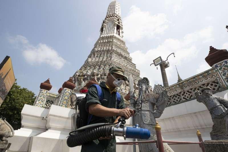 泰國的武漢肺炎疫情延燒,工作人員在曼谷知名觀光勝地鄭王廟消毒(美聯社)